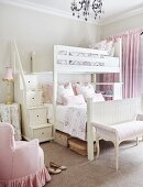 Antique furniture upholstered in delicate pink and storage stairs leading to bunk beds in romantic girls' bedroom
