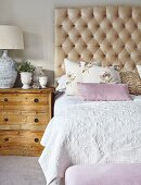 Double bed with button-tufted headboard, structured bedspread and floral scatter cushions next to rustic, county-house chest of drawers
