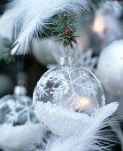 Baumkugel aus Glas gefüllt mit Styroporkügelchen und bemalt mit Schneeflockenmotiven
