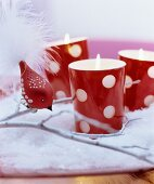 Weihnachtsdeko in Rot-Weiss: Rote gepunktete Windlichter auf Kunstschnee