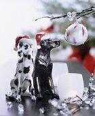 Zwei schwarz-weisse Hundefiguren mit Nikolausmützen als weihnachtliche Dekoration neben Zweigen verziert mit Glasperlen