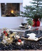 Couchtisch aus Plexiglas auf schwarzem Designerteppich aus Lederstreifen in weihnachtlich dekoriertem Wohnraum mit Kamin