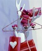 Drahtbügel weihnachtlich dekoriert mit Dekopilzen und Weihnachtspäckchen aufgehängt an Metallgarderobe in Geweihform