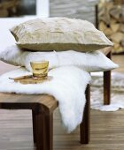 Fur cushion and sheepskin blanket on wooden bench