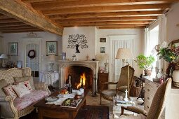 Comfortable living room with open fire, wood-beamed ceiling, curved couch and coffee table in old country house