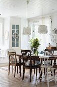 Various chairs around antique wooden table in kitchen