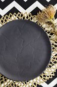 Grey plate on gold place mat (festive)