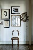 Thonet chair below framed pictures on wall