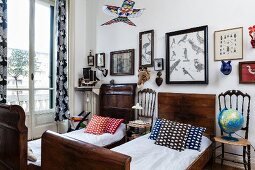 Patterned scatter cushions on twin, antique sleigh beds made from dark wood and chairs used as bedside tables below framed pictures of birds on wall