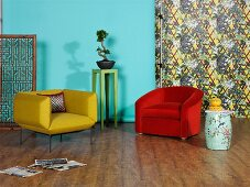 Retro armchairs in yellow and red, Chinese porcelain accessories and Bonsai tree against turquoise wall and patterned wallpaper