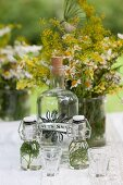 Herbs in swing-top bottles, large corked bottle and vase of flowers on garden table