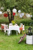 Garden table set for Swedish crayfish party under lanterns hung from tree