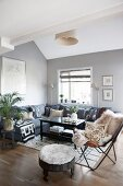 Ethnic accessories and grey corner sofa in living room