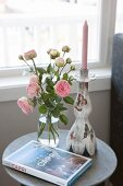 Vases of roses, book about Capri and candlestick on side table