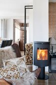 Sheepskin rug and ethnic cushions on leather armchair in front of log burner