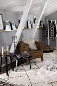 Leather armchair and side tables under pictures on narrow shelf and sloping ceiling