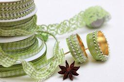 Grüne Geschenkbänder und beklebte Kerzenhalter für Adventskranz