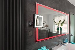 A wall mirror with integrated red LED lighting on a grey-tiled wall