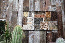 Künstlerisch gestaltetes Insektenhotel aus Naturmaterialen an Bretterwand