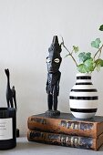 African figurines and striped vase on top of two old books