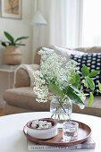 White umbels in glass vase on wooden tray