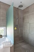 A shower cabin with a rain shower head and grey wall tiles in a designer bathroom