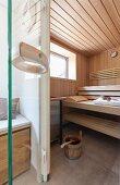 Blick in edlen Saunabereich mit Fenster und Saunautensilien