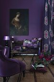 Scatter cushions on antique wooden bench, retro lamp on side table and oil painting of woman on wall painted aubergine