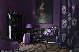 Room in shades of purple: armchair with mauve cover, antique bench below oil painting on aubergine wall and patterned curtain to one side
