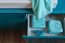 Folded, turquoise towels and washing utensils in an open drawer in a washstand