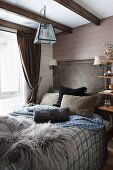 Fur rug and scatter cushions on comfortable bed in rustic bedroom with wood-clad walls and wood-beamed ceiling