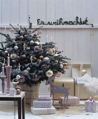 Festively decorated room with Christmas tree, gifts & candles