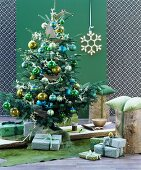 Festively decorated room in shades of green with Christmas tree, presents and tree stump stools