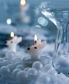 Reindeer-shaped tealights surrounded by white baubles & glass vase