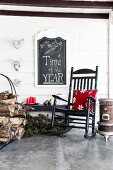 Red floral cushion on rocking chair, stacked firewood and candles on roofed veranda: motto on chalkboard on wall