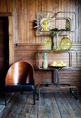 Curved metal shelving and designer chair in front of board wall