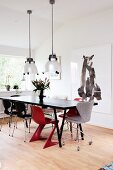 Black retro dining table, two red chairs and industrial pendant lamps in Scandinavian dining room