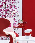 Red chair, red and white side tables, white orchid, red wall and picture with Japanese floral motis