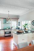 Modern, open-plan, white kitchen with black stone worksurfaces on U-shaped counters and stucco ceiling