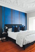 Elegant bedroom with black double bed and arranged scatter cushions, blue and black striped wallpaper and white stucco ceiling