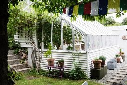 Potted plant and crates outside greenhouse with white weatherboard façade