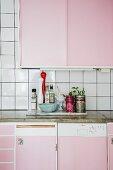 Küchenzeile mit rosa Schrankfronten und Arbeitsplatte aus Beton