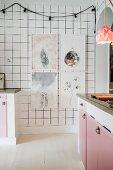 Weisse Fliesenwand mit gerahmten Bildern und Lichterkette in einer Küche