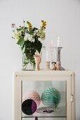 Blumenstrauss in Glasvase neben Kerzenhalter mit brennenden Kerzen, auf Retro Vitrinenschrank, Dekokugeln aus Papier auf Glasablage