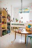 Runder Holztisch mit Spielsachen auf weissem Dielenboden, seitlich Regale in Hausform, neben weissem Bett am Fenster im Kinderzimmer