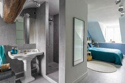 Grey shower area in ensuite bathroom with view into blue bedroom in renovated attic with dormer window