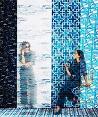 Pattern mix in shades of blue: Young woman in front of different tracks of wallpaper with different graphic motifs