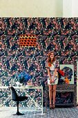 Young woman in room with different patterns on wallpaper, carpet, lampshade and dress