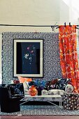 Living room with a mix of floral patterns on wallpaper, curtain, sofa and pillows