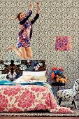 Young woman jumping on bed in room with different patterns